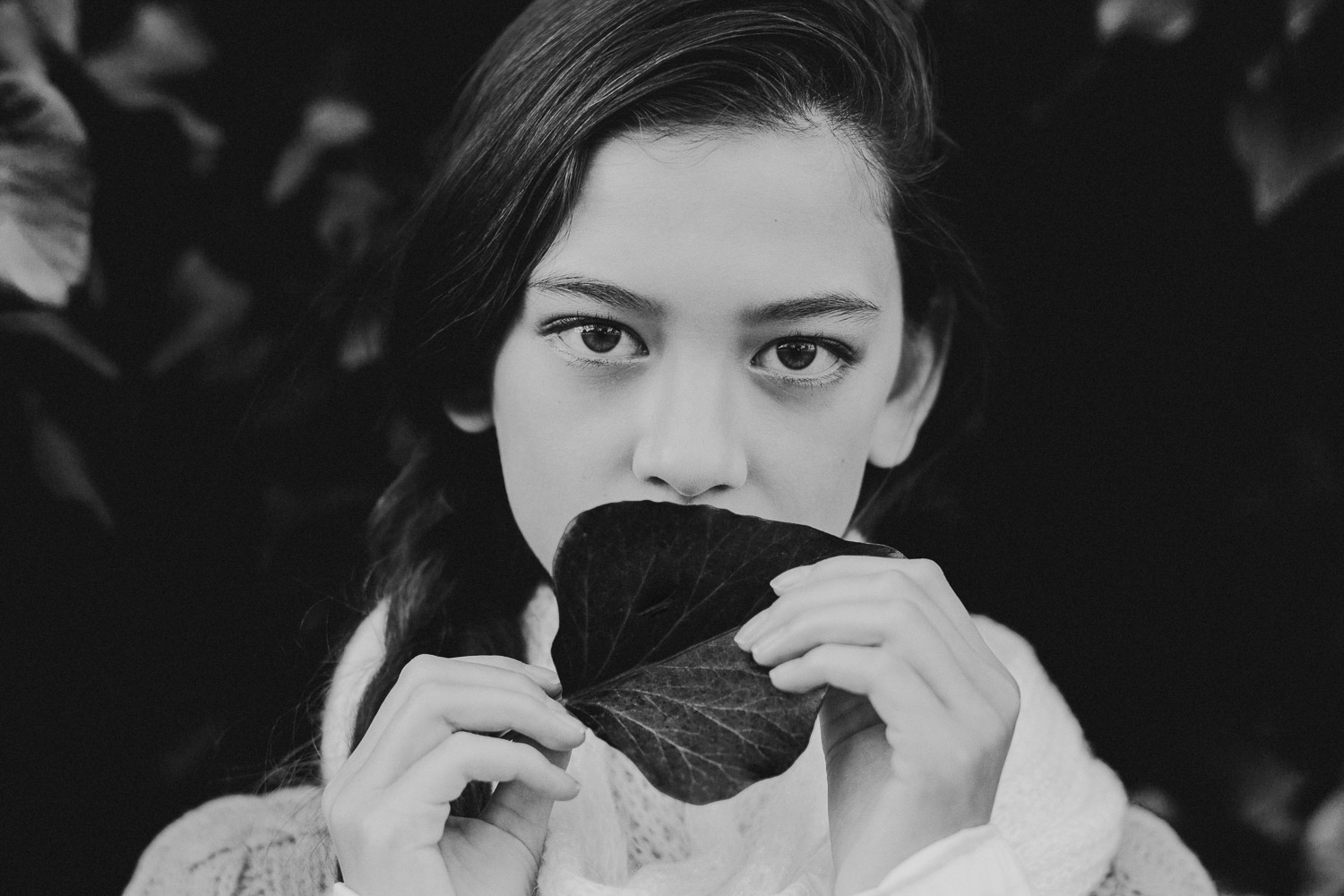 Black and White image of girl covers her mouth with a leaf