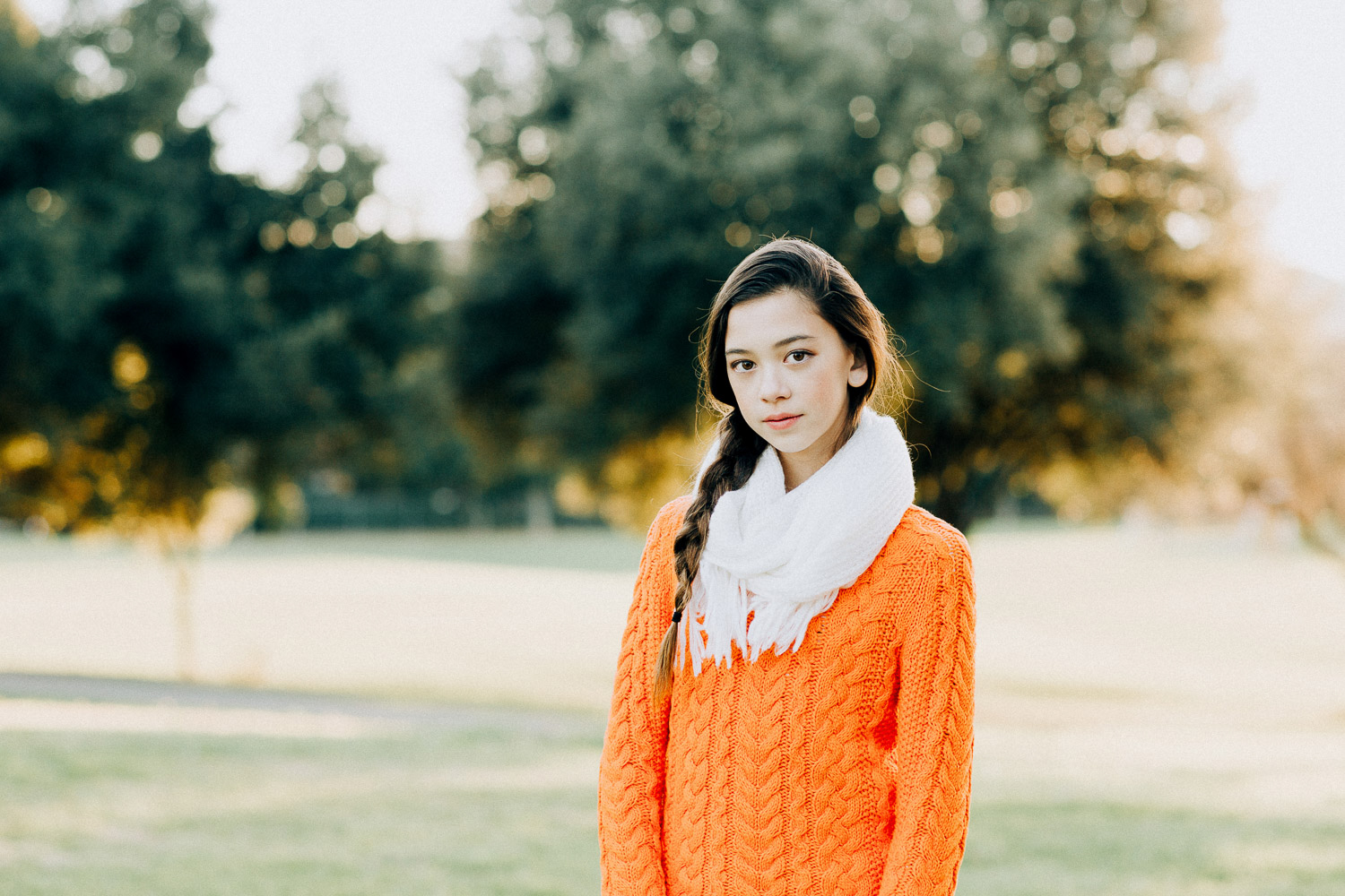 Image of a teenage girl wearing an orange sweater in front of trees