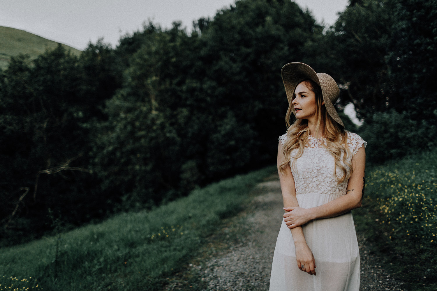 Image of bride wears a hat and looks to the left