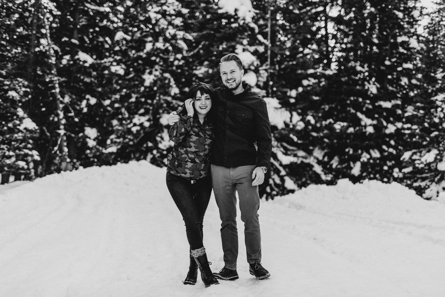 Black and White image of couple stand together in snow