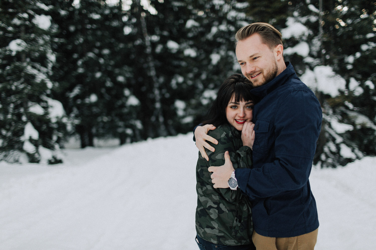 Image of couple hug each other in snow
