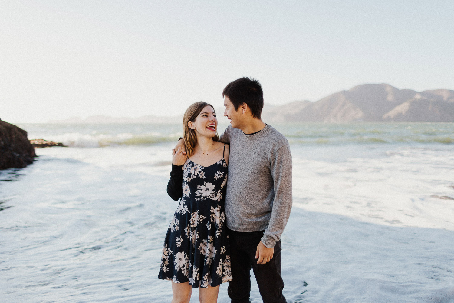 Image of couple smile to each other on beach