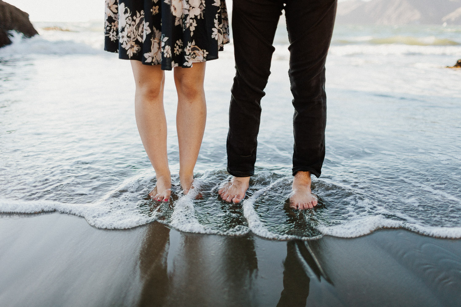 Image of couple's feet in water on beach