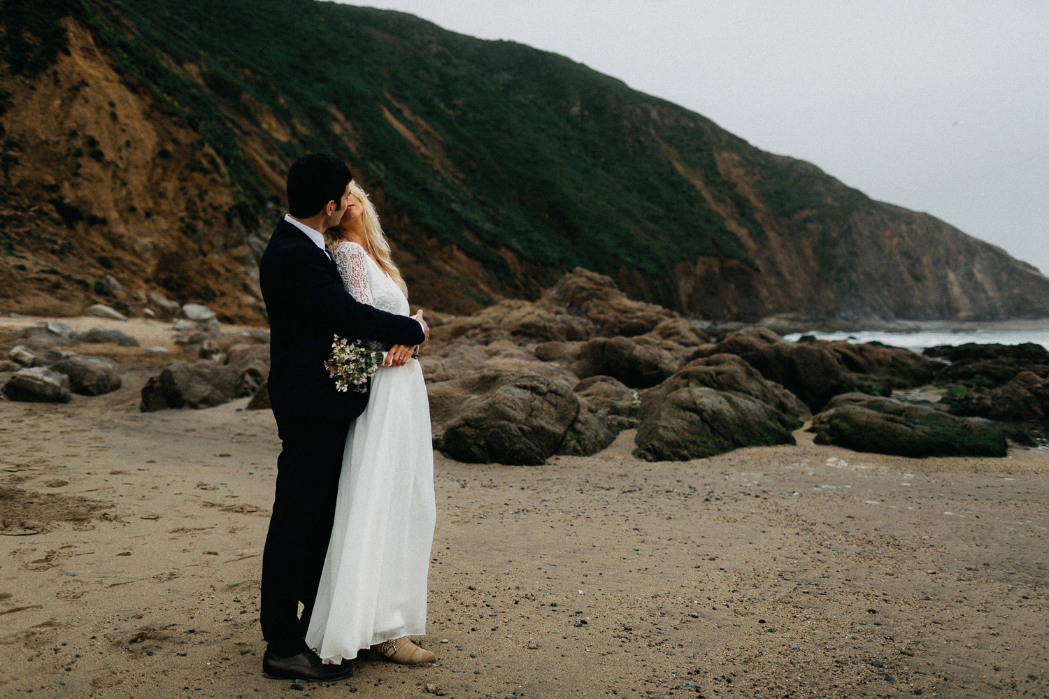 Image of groom kisses bride on beach