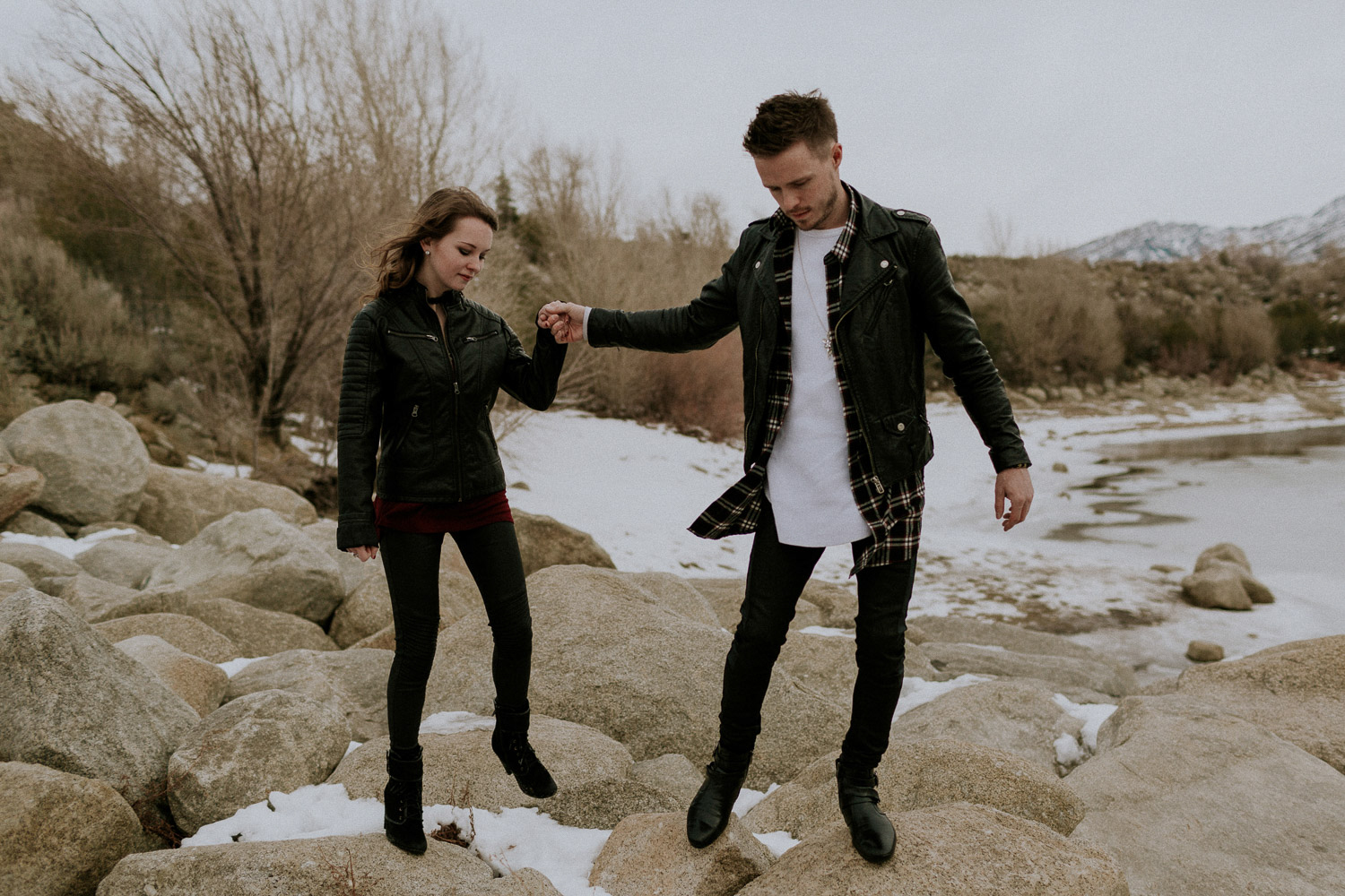 Image of couple hold hands together walking on rocks