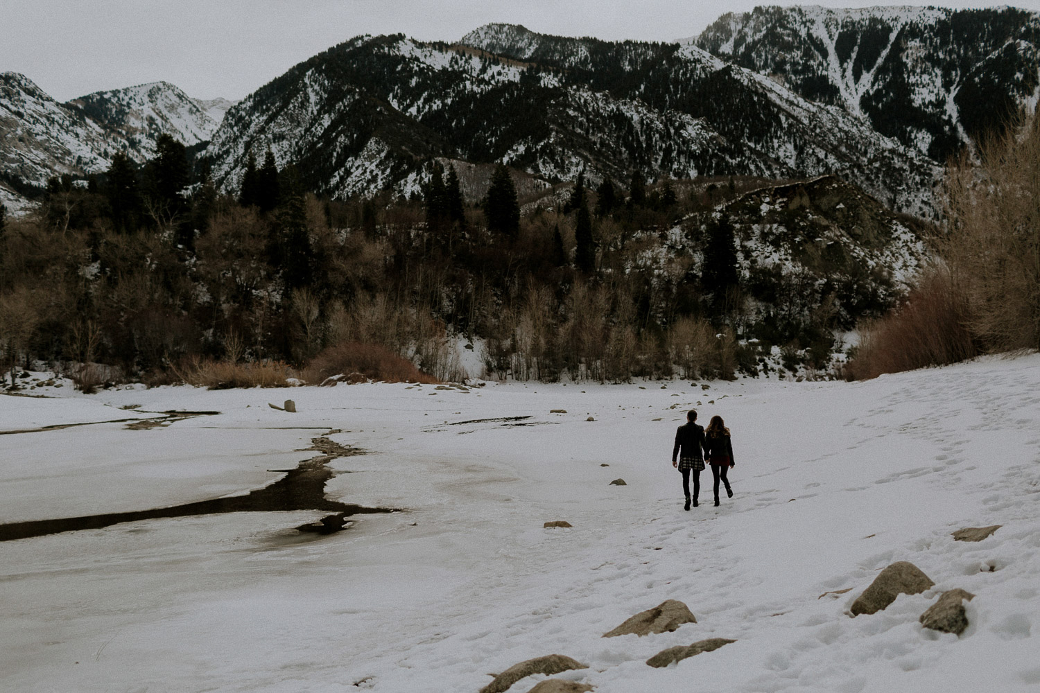 Image of couple walk together in snow towards the mountain