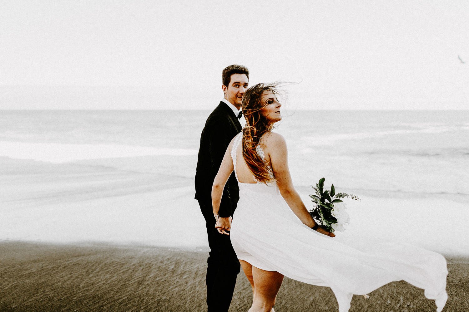 Image of groom and bride hold hands on beach