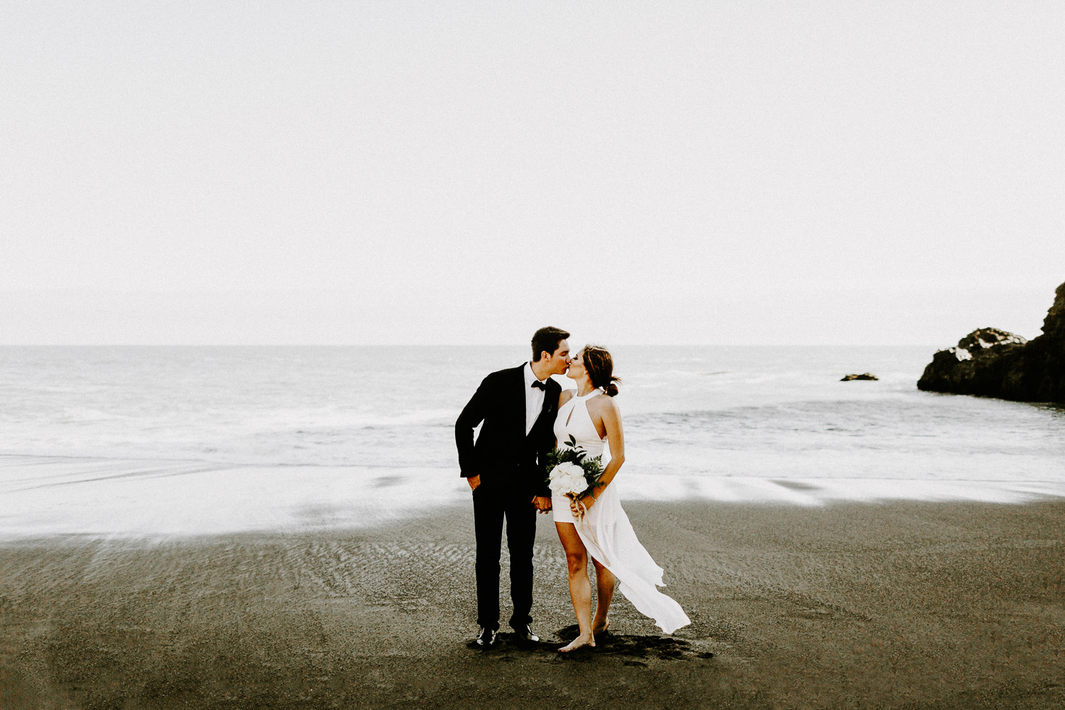 Image of groom and bride kiss each on beach