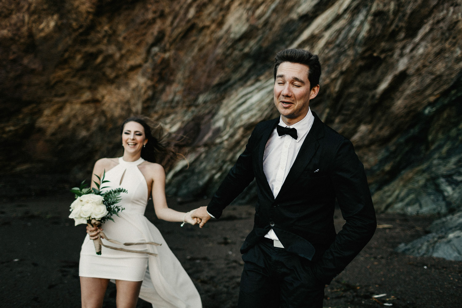 Image of groom leads bride to walk on beach